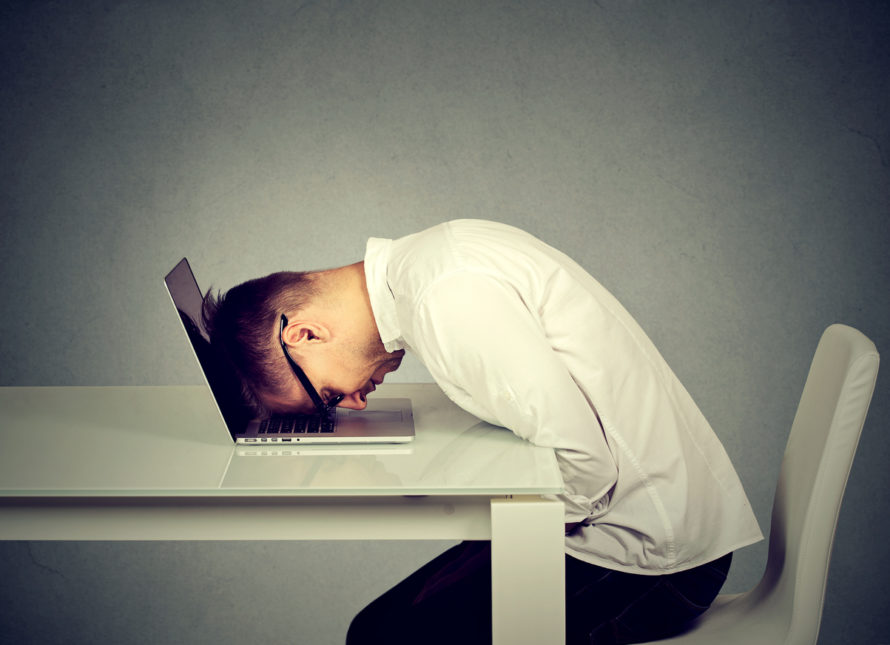 A man rests his head on his laptop against a grey background