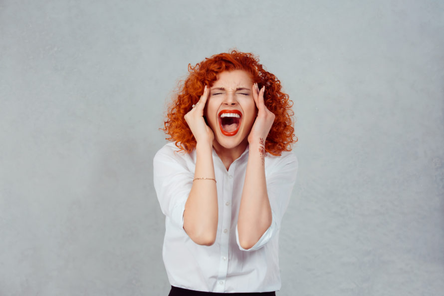 A very stressed redheaded woman is screaming on a grey background